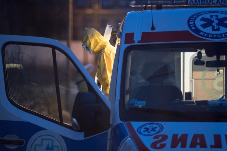 Ratownik w kombinezonie wysiada z karetki w czasie koronawirusa