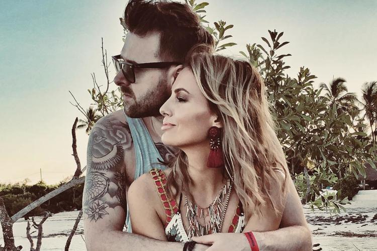 Grzegorz Hyży w okularach i Agnieszka Hyży w jego objęciach siedzą na plaży na wakacjach w ciepłych krajach