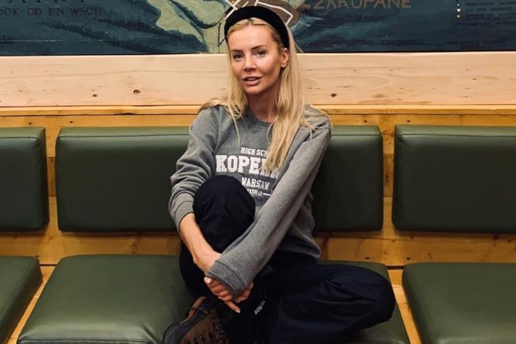 Agnieszka Woźniak-Starak w szarej bluzie i czarnej opasce w schronisku w górach