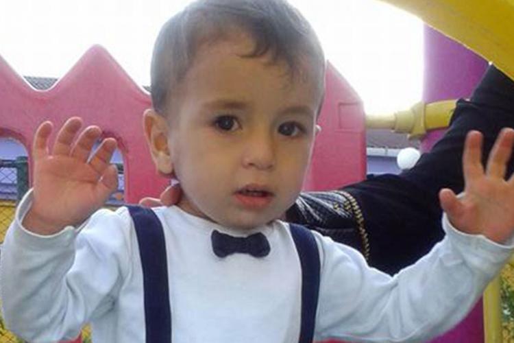 Alan Kurdi w koszuli i z szelkami na placu zabaw