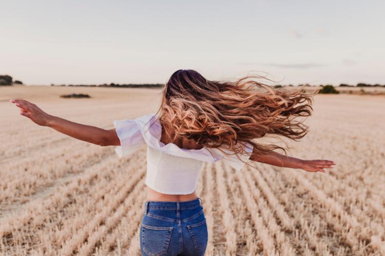Młoda dziewczyna z długimi włosami na polu kręci się dookoła własnej osi
