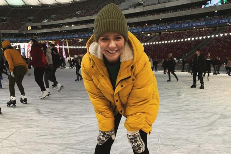 Aneta Zając w żółtej kurtce, zimowej czapce i rękawiczkach na lodowisku