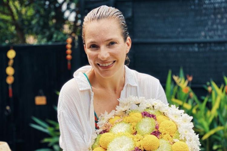 Anna Dereszowska uśmiechnięta z bukietem kwiatów na basenie w Wietnamie
