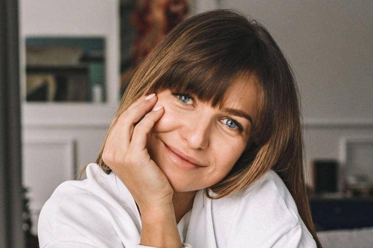 Anna Lewandowska uśmiechnięta w białej bluzie siedzi przy stole