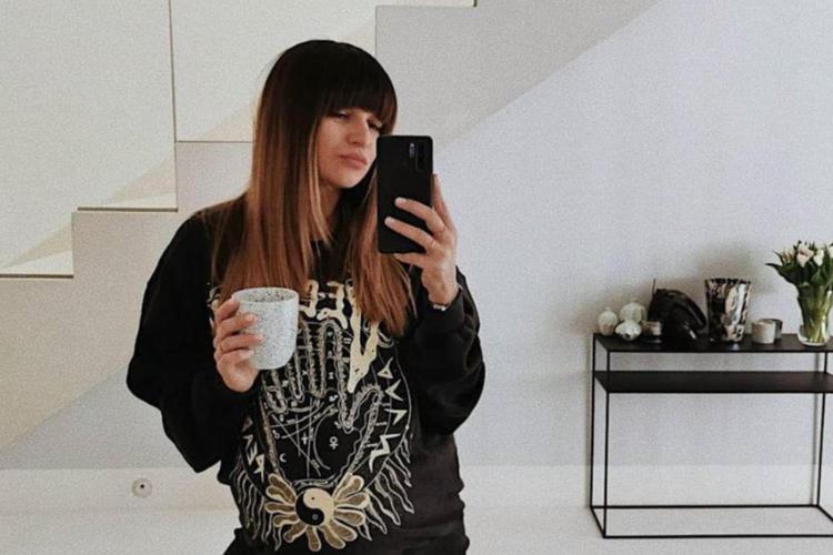 Anna Lewandowska w ciąży w czarnej szerokiej bluzie i z kubkiem kawy robi sobie selfie w lustrze