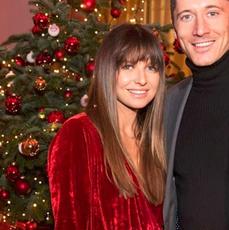 Anna Lewandowska w czerwonej welurowej sukience i Robert Lewandowski w garniturze przy choince podczas imprezy świątecznej FC Bayern