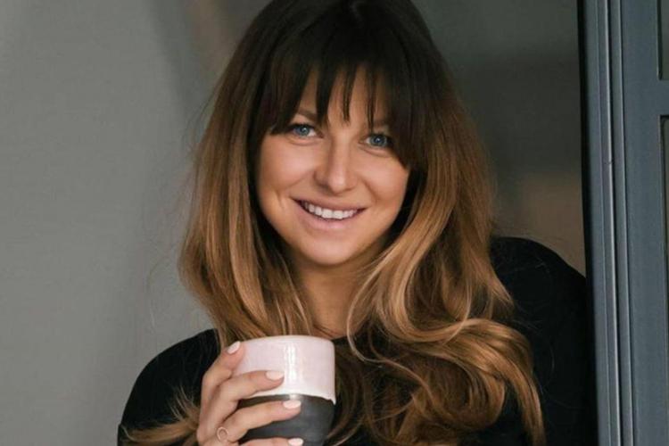 Anna Lewandowska uśmiechnięta w czarnym swetrze z kubkiem kawy w ręce