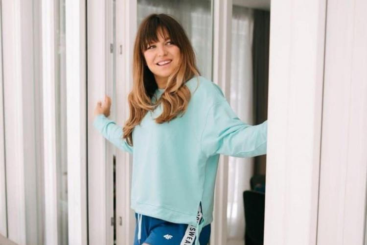 Anna Lewandowska uśmiechnięta, w miętowej bluzie idzie przez drzwi balkonowe
