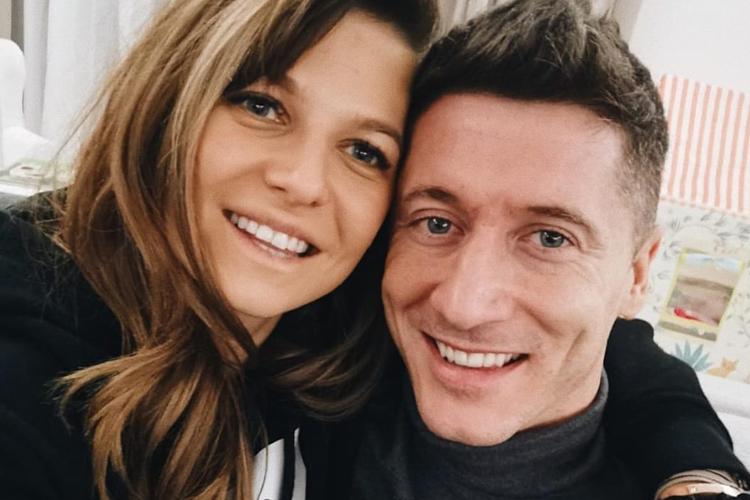 Anna Lewandowska w bluzie i Robert Lewandowski w golfie przytulają się do siebie