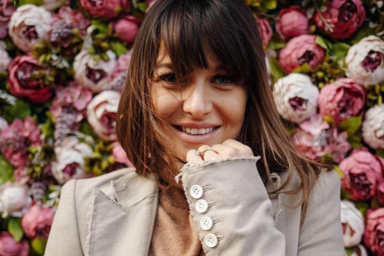 Anna Lewandowska uśmiechnięta w beżowej marynarce na tle kwiatów