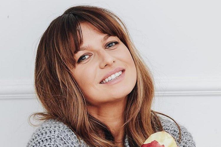 Anna Lewandowska uśmiechnięta w szarym swetrze i z jabłkiem w ręce