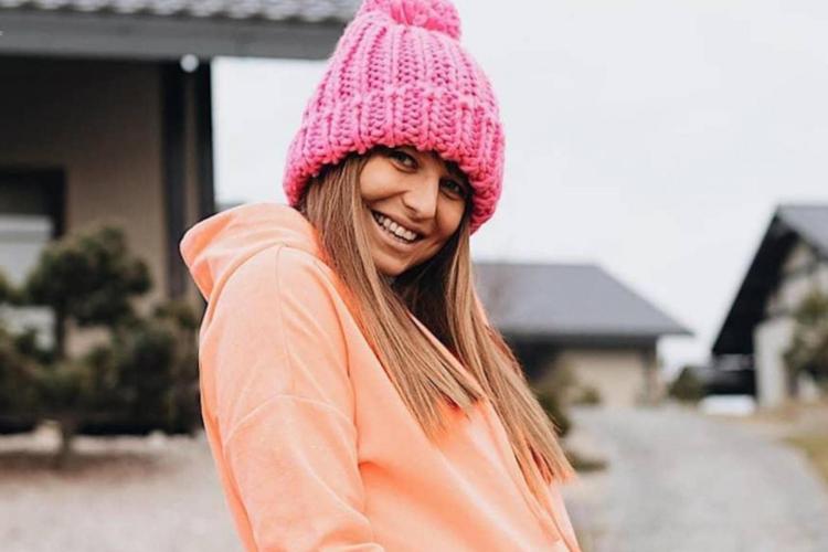 Anna Lewandowska w pomarańczowej bluzie i różowej czapce