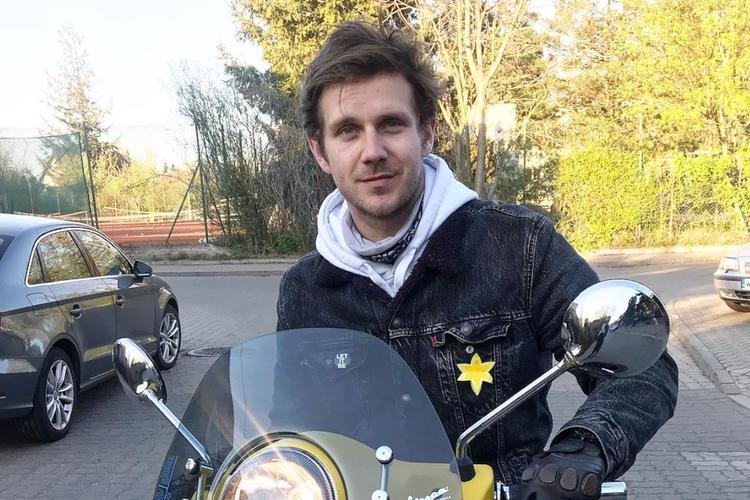 Antek Królikowski w kurtce na żółtym skuterze