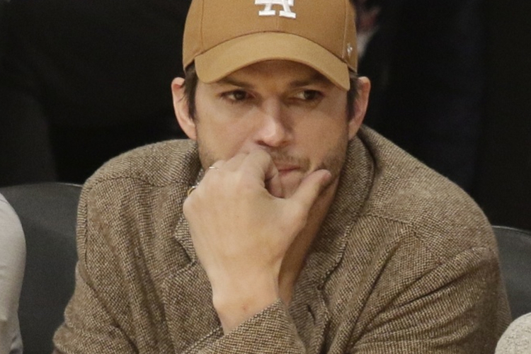 Ashton Kutcher w brązowej czapce na trybunach podczas meczu
