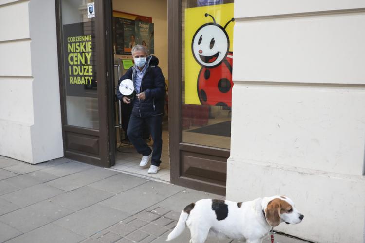 Starszy mężczyzna w maseczce ochronnej wychodzi z zakupami ze sklepu Biedronka