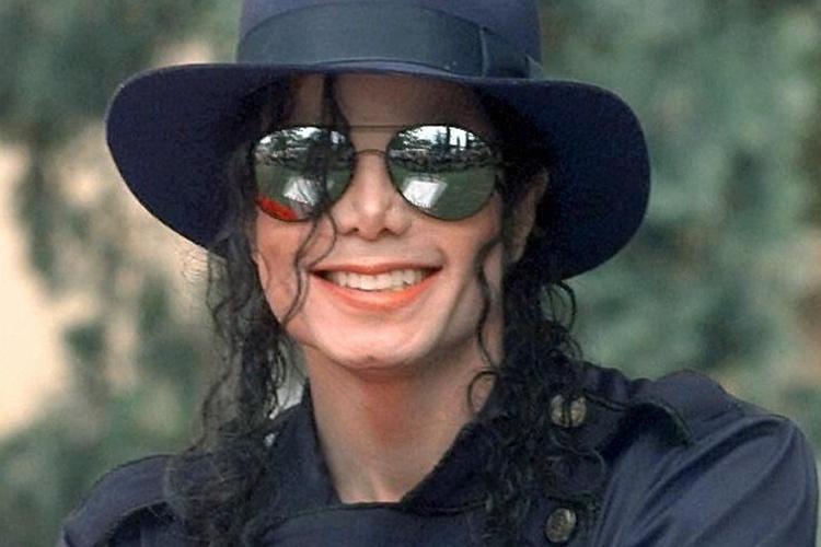 Michael Jackson uśmiechnięty w okularach przeciwsłonecznych i kapeluszu