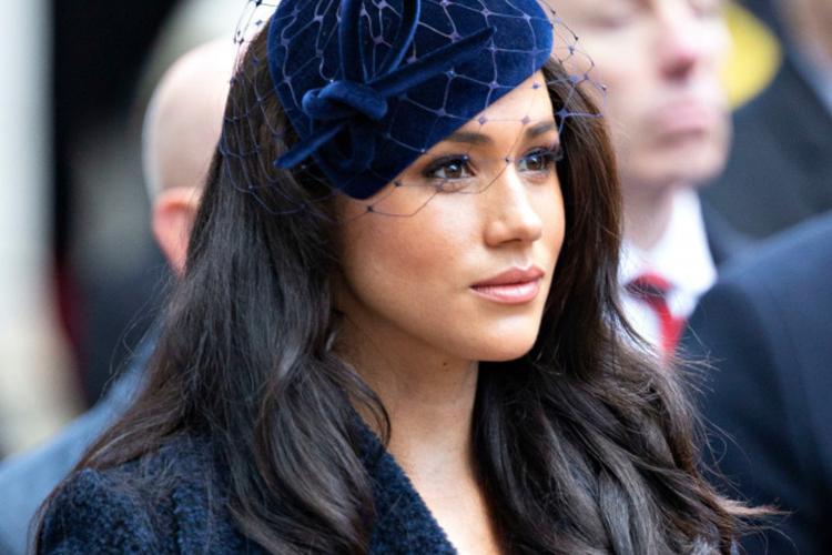 Księżna Meghan w granatowym kożuszku i granatowym kapeluszu z woalką