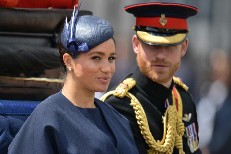Księżna Meghan w kapeluszu i książę Harry w mundurze jadą powozem
