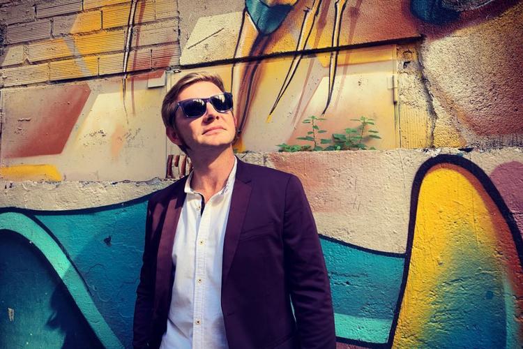 Rafał Zawierucha w marynarce i okularach przeciwsłonecznych na tle graffiti