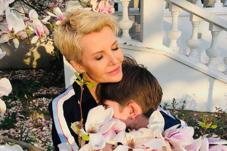 Joanna Racewicz wśród kwiatów przytula syna