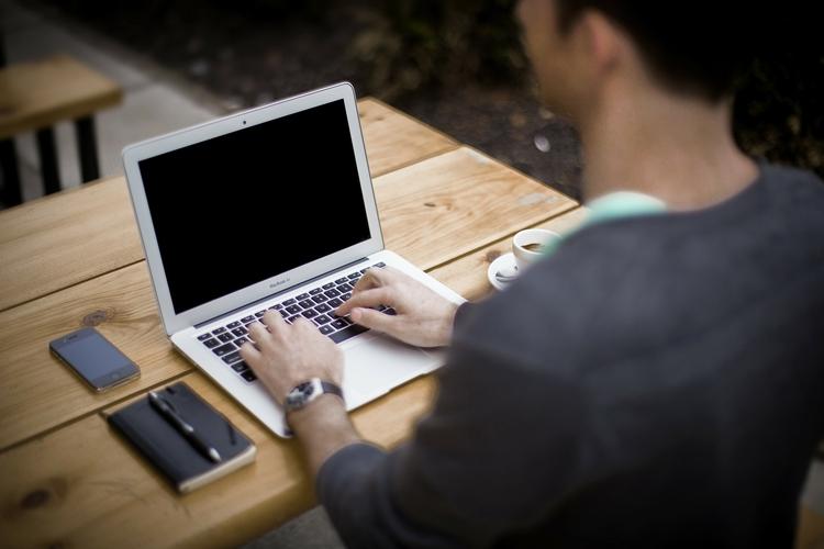 Człowiek piszący na laptopie