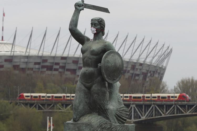 Koronawirus w Polsce: warszawska Syrenka w maseczce na tle Wisły, mostu kolejowego i Stadionu Narodowego