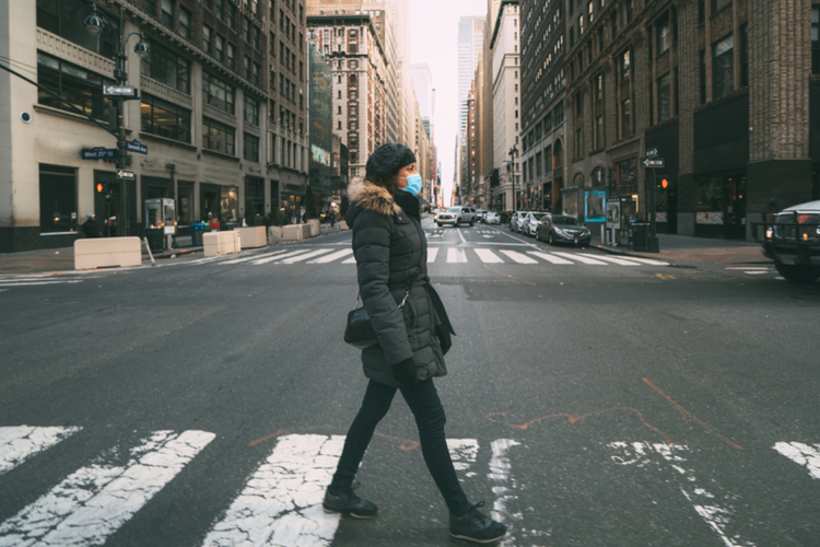 Kobieta w maseczce spaceruje ulicą w dobie koronawirusa