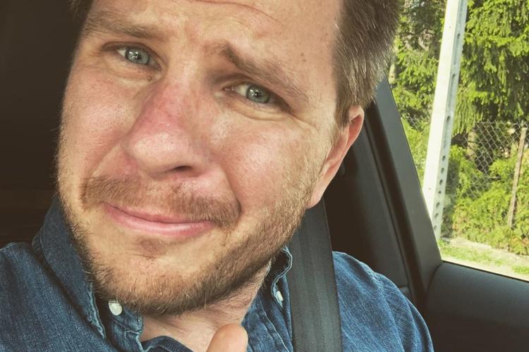Filip Chajzer zadowolony jedzie samochodem i pokazuje kciuk do góry