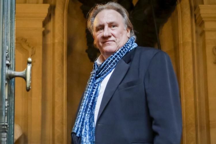 Gérard Depardieu w garniturze i z apaszką uśmiecha się deliktanie
