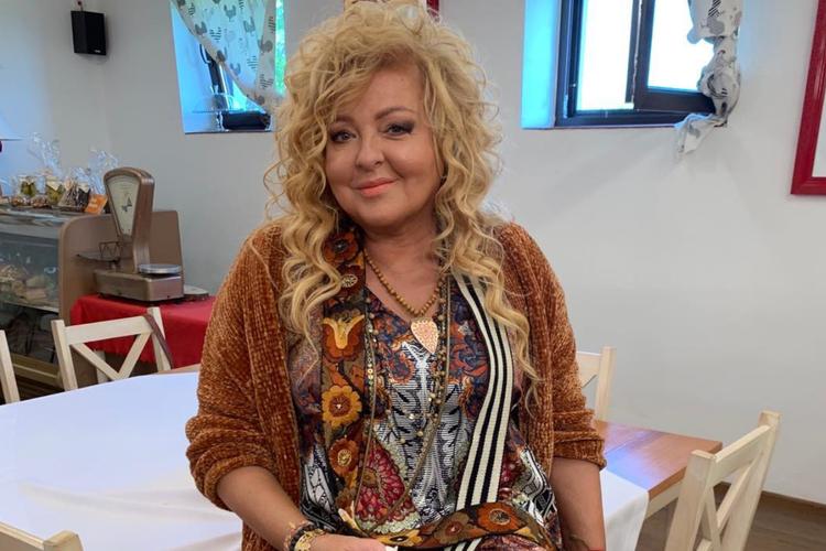 Magda Gessler w kolorowej sukience siedzi na stole