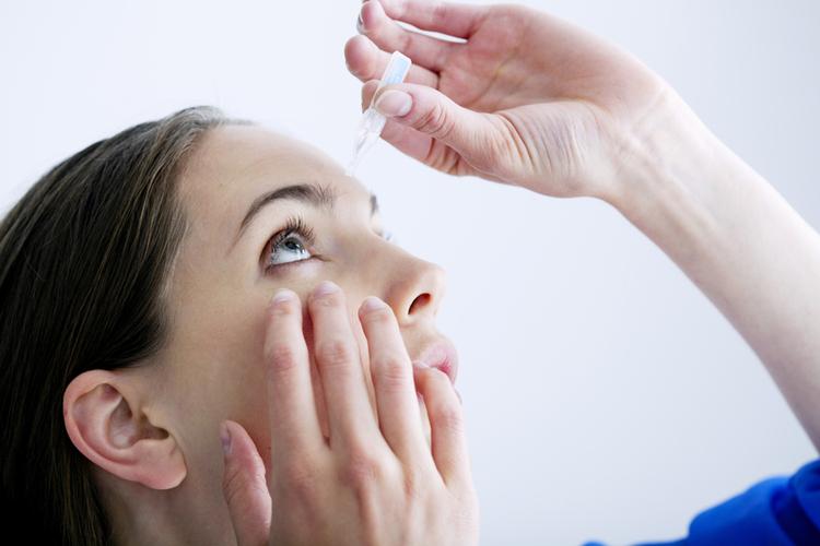 kobieta aplikująca krople do oczu