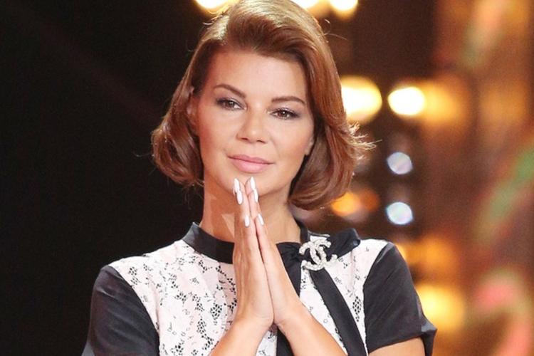 Edyta Górniak ze złożonymi rękami w czarnej sukience podczas koncertu Tribute To Wodecki