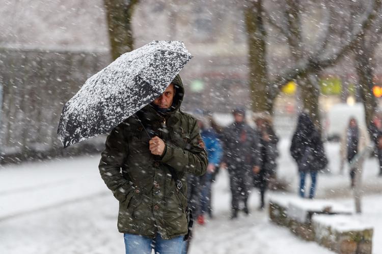 mężczyzna chroniący się parasolem przed śnieżycą