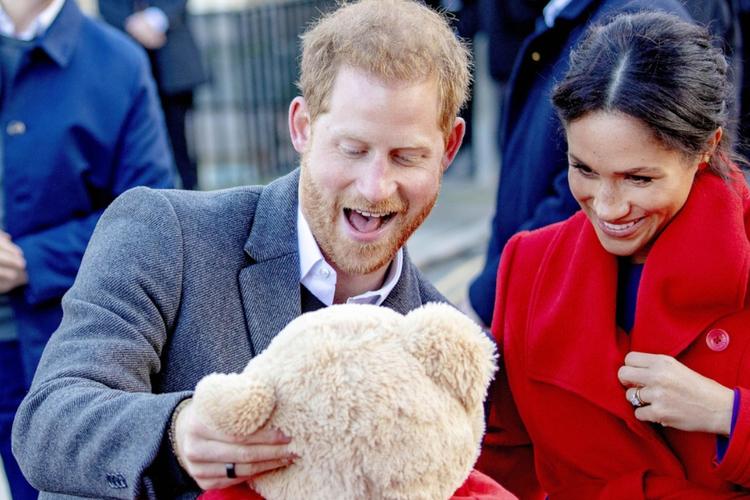 Książę Harry i księżna Meghan w czerwonym płaszczu cieszą się i patrzą na pluszowego misia, którego Harry trzyma w rękach