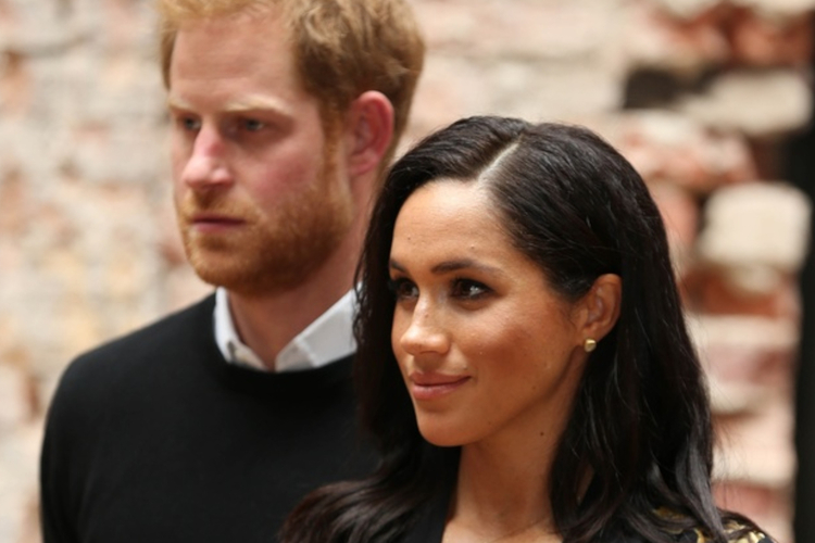 Księżna Meghan w czarnej sukience, a w tle książę Harry w koszuli i czarnym sweterku