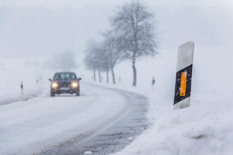 Na zaśnieżonej drodze porusza się samochód osobowy.
