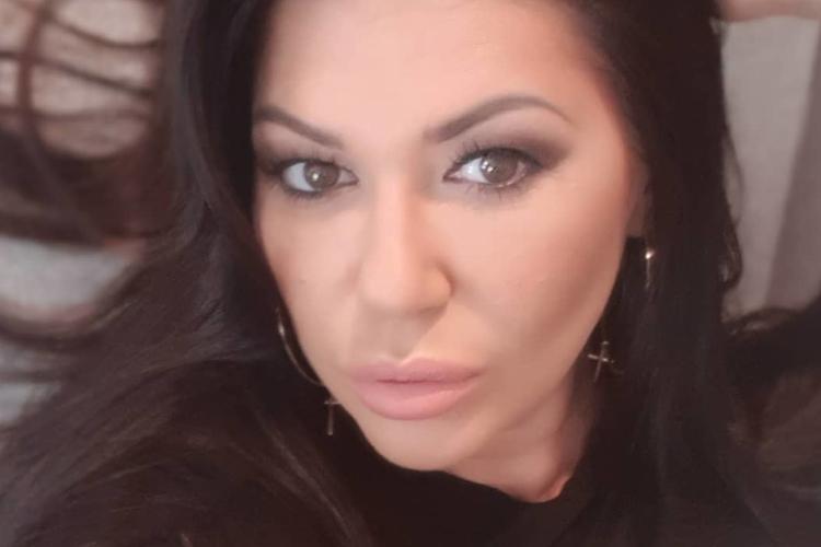 Iwona Węgrowska w czarnej bluzie, ze srebrnymi kolczykami, robi sobie selfie