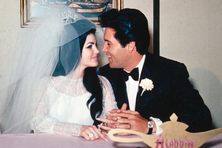 Priscilla Presley w białej sukni i welonie oraz Elvis Presley w smokingu patrzą sobie w oczy podczas wesela