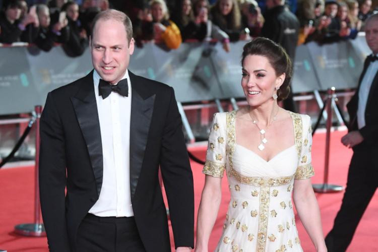 Książę William we fraku i księżna Kate w białej sukni ze złoceniami na czerwonym dywanie podczas BAFTA 2020