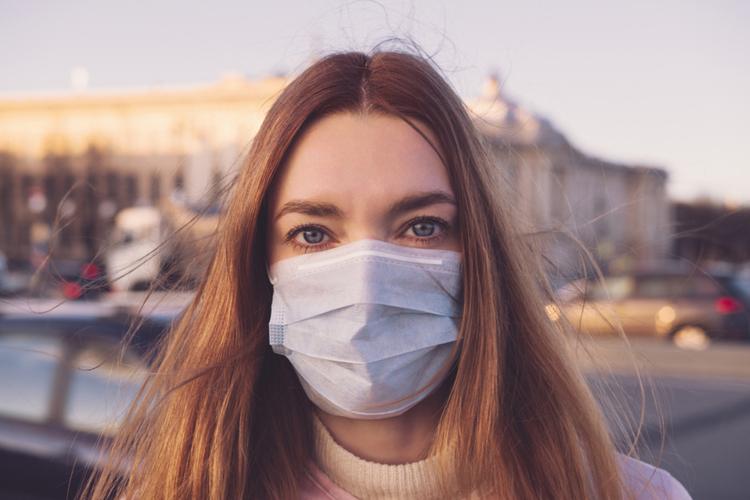 Młoda kobieta z długimi włosami w maseczce próbuje chronić się przed koronawirusem
