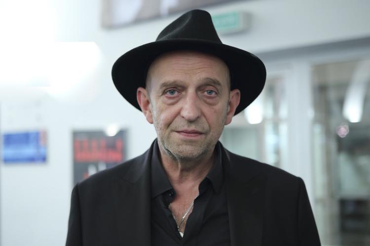 Janusz Chabior w czarnej koszuli, marynarce i kapeluszu pozuje do zdjęcia