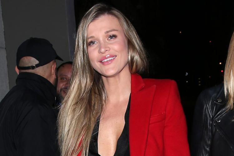 Joanna Krupa uśmiechnięta w czarnej bluzce i czerwonym płaszczu