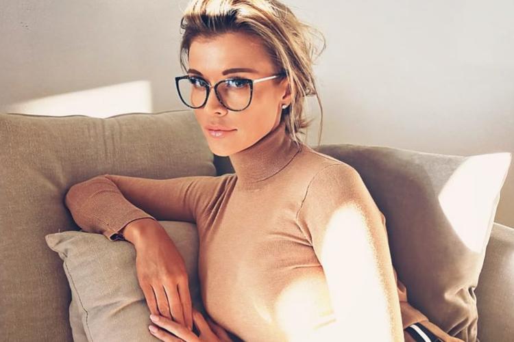 Joanna Krupa siedzi na kanapie w okularach