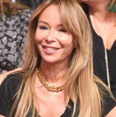 Joanna Przetakiewicz w czarnej bluzce siedzi na krześle