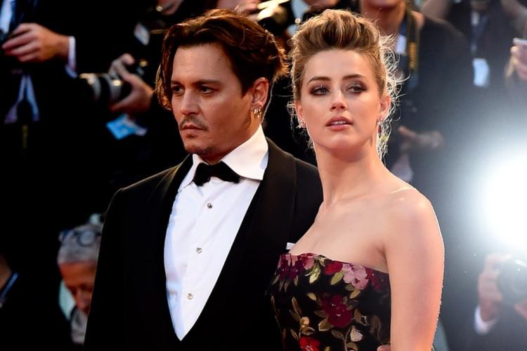 Amber Heard w kwiecistej sukience i Johnny Depp w garniturze pozują na czerwonym dywanie