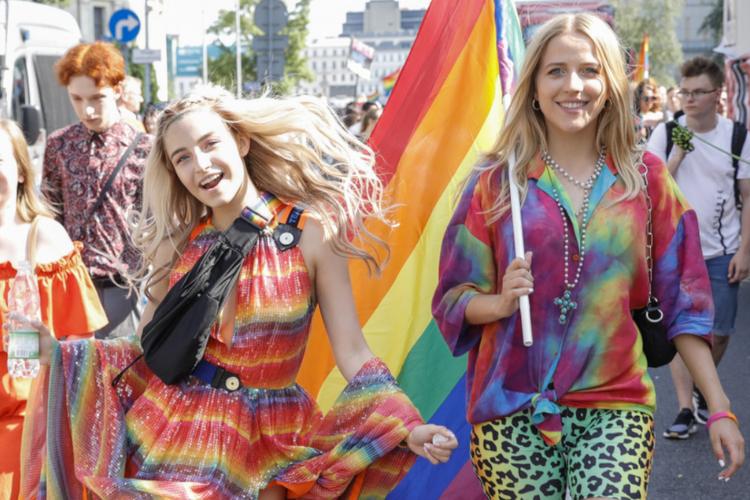 Julia Wieniawa w tęczowej sukience i blond peruce i Jessica Mercedes w tęczową flagą na Paradzie Równości
