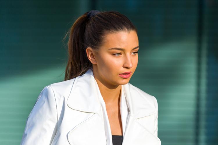 Julia Wieniawa zamyślona w kucyku i białym płaszczu