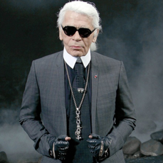 Karl Lagerfeld w ciemnych okularach, stalowym garniturze i skórzanych rękawiczkach