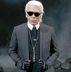 Karl Lagerfeld w ciemnych okularach, stalowym garniturze i skórzanych rękawiczkach