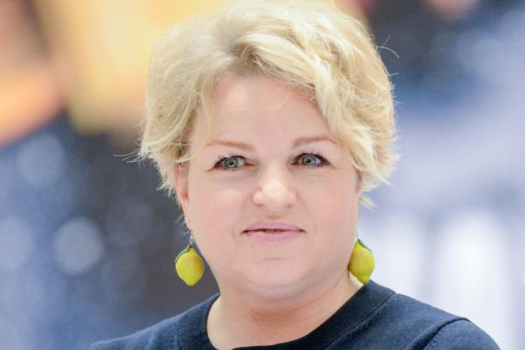 Katarzyna Bosacka w czarnej sukience z żółtymi kolczykami w kształcie cytryn